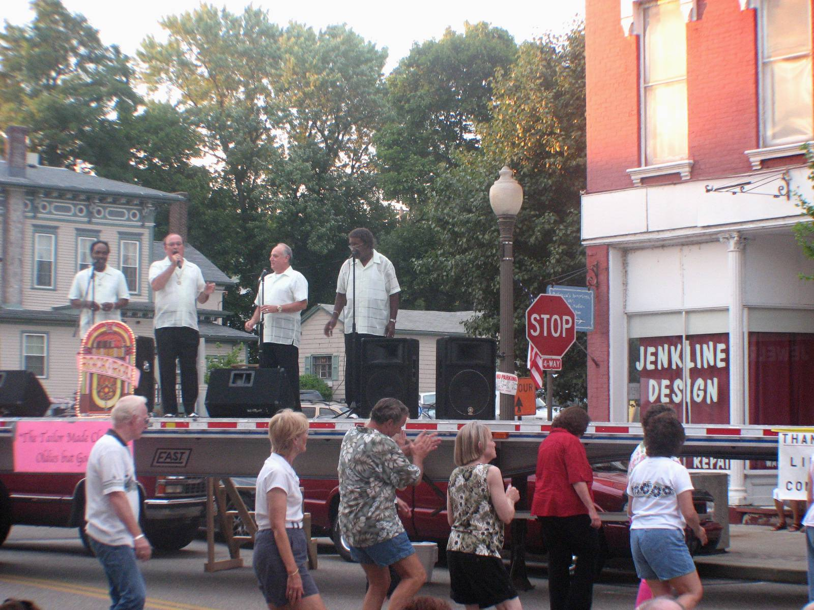 The Taylor Made Classics sing while spectators dance in the street to their old favorite songs.